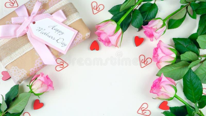 Moeder` s Dag lucht met gift en roze rozen op witte houten lijstachtergrond royalty-vrije stock fotografie
