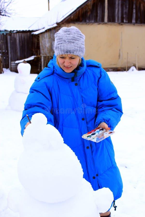 Moeder schilderende sneeuwman Het genieten van de winter van vakantie De vakanties van de de winterfamilie stock afbeeldingen