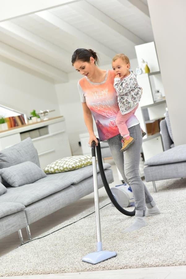 Moeder schoonmakende vloer met baby in haar wapens stock afbeelding