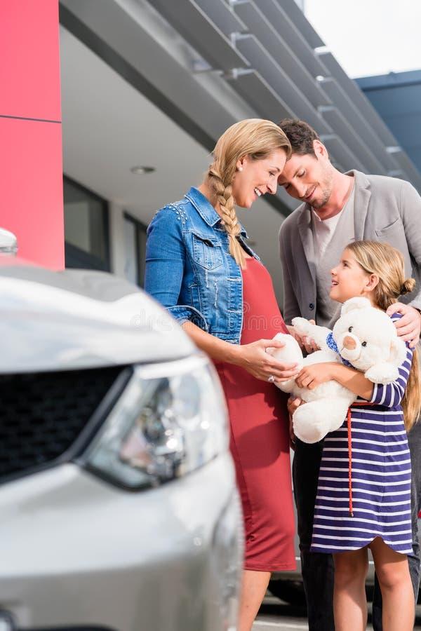 Moeder, vader, en kind het kopen auto bij het handel drijven stock afbeeldingen
