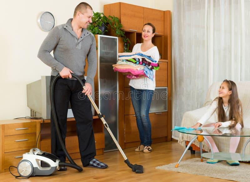 Moeder, vader en meisje die het algemene schoonmaken doen royalty-vrije stock fotografie