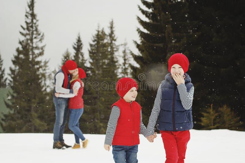 Moeder, vader en twee zonen die pret in de sneeuwwinter hebben royalty-vrije stock fotografie