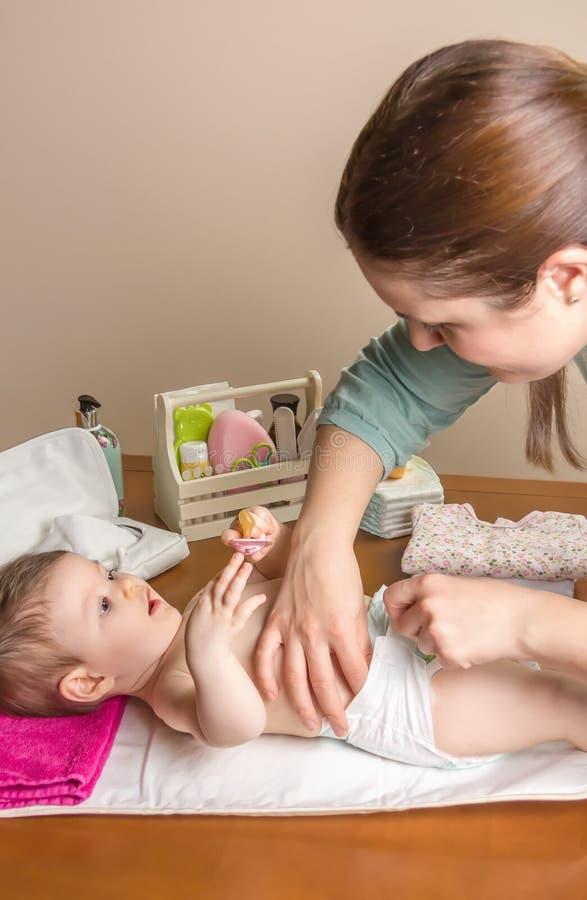 Moeder veranderende luier van aanbiddelijke baby stock fotografie
