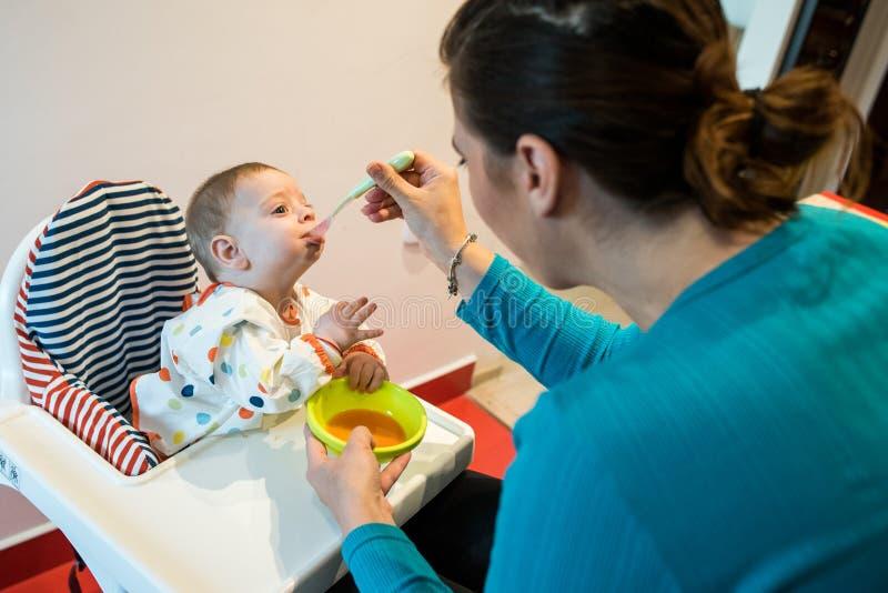 Moeder voedende baby eerste stevig voedsel voedseldiversificatie stock afbeeldingen