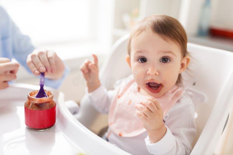 Moeder voedende baby met puree thuis royalty-vrije stock fotografie
