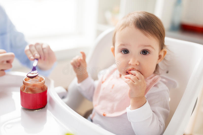 Moeder voedende baby met puree thuis stock foto