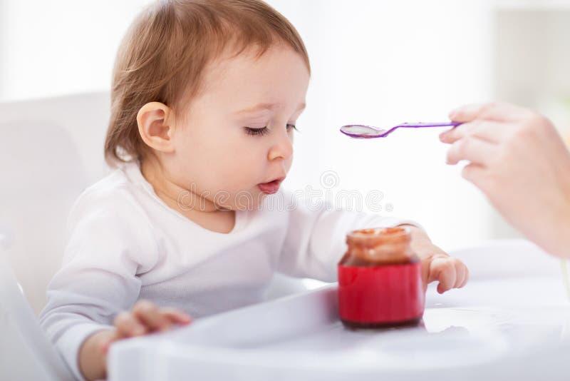 Moeder voedende baby met puree thuis royalty-vrije stock foto