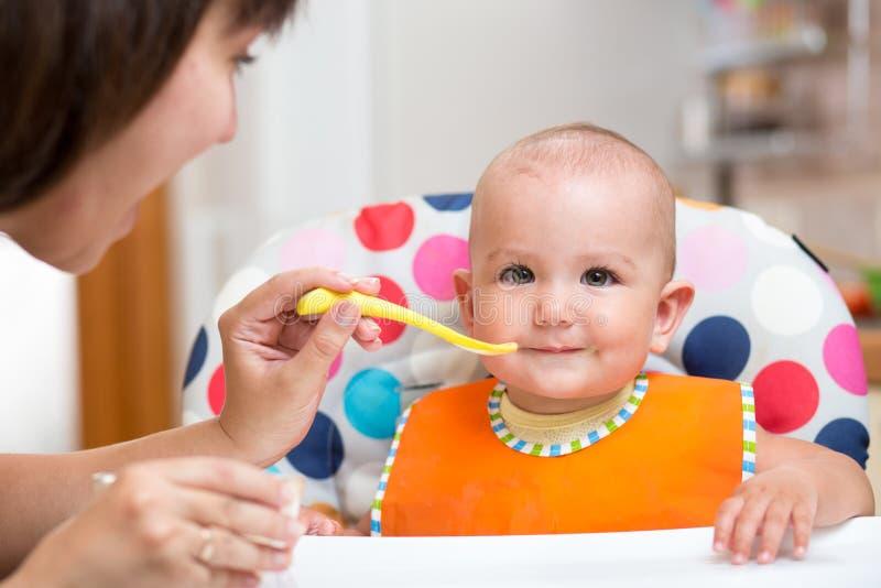 Moeder voedende baby op keuken stock afbeeldingen