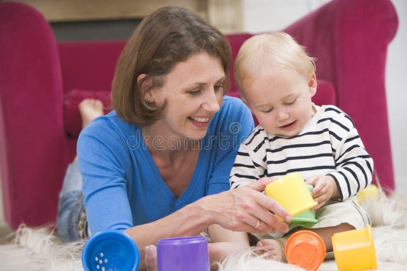 Moeder in woonkamer het spelen met baby royalty-vrije stock afbeeldingen