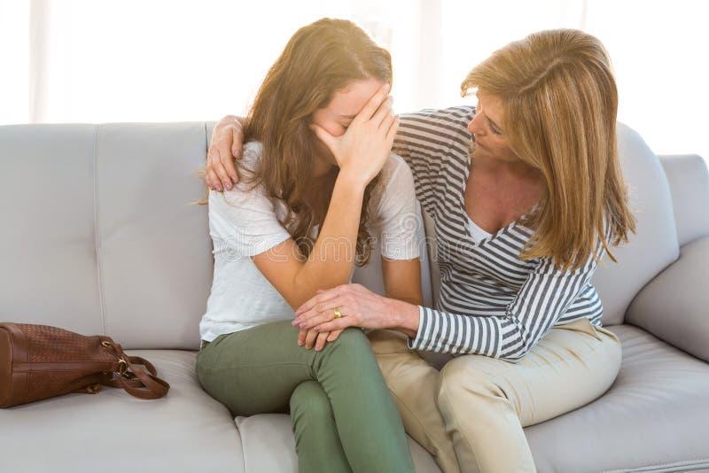 Moedercomfort haar dochter stock foto