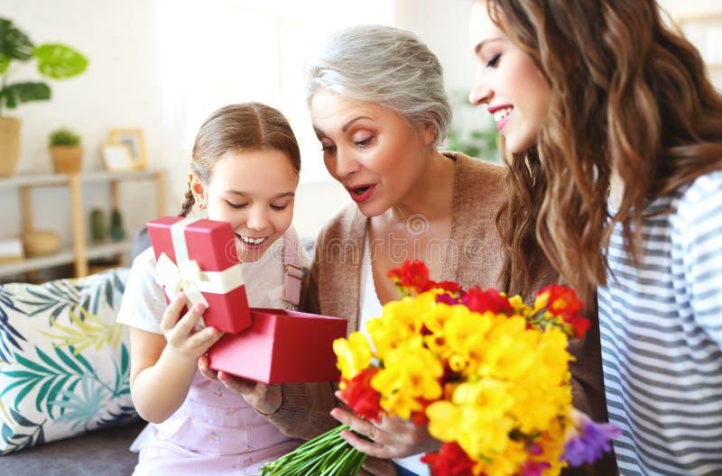 Moederdag! drie generaties van familiemoeder, grootmoeder en dochter wensen met de vakantie geluk, geven bloemen royalty-vrije stock afbeelding