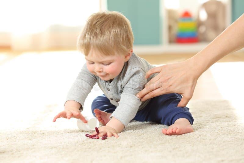 Moederhand die de baby verhinderen pillen te eten stock afbeeldingen