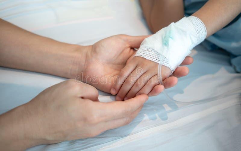 Moederhanden die haar baby geduldige hand met Zoute intraveno houden royalty-vrije stock afbeeldingen