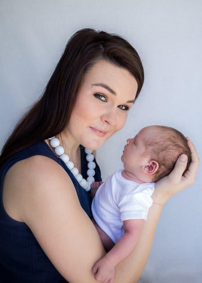 Moederholding die pasgeboren baby slapen die camera het glimlachen bekijken royalty-vrije stock afbeelding