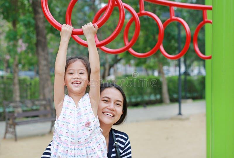Moederhulp haar dochter aan het spelen op gymnastiek- ring op speelplaats openlucht stock afbeelding