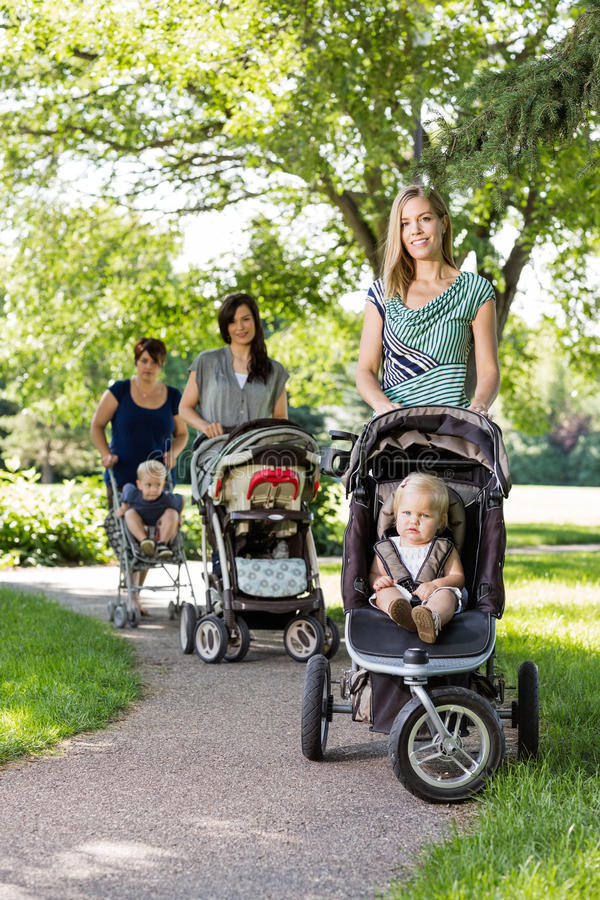 Moeders die Babywandelwagens in Park duwen stock foto's
