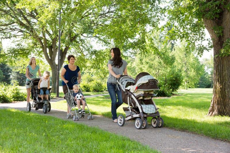 Moeders die met Kinderwagens in Park lopen stock afbeelding