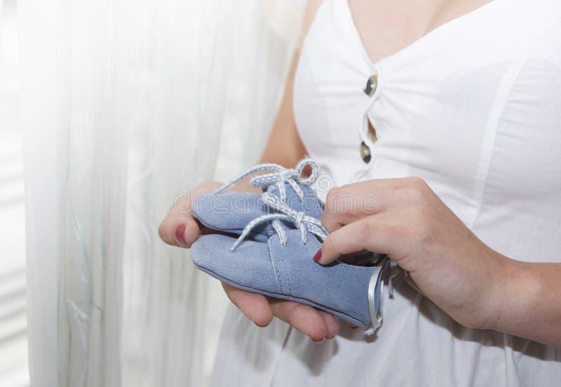 moederschap De handen van de babyschoenen van de vrouwenholding sluiten omhoog Concept eenheid, steun, bescherming en geluk Toeko royalty-vrije stock foto's