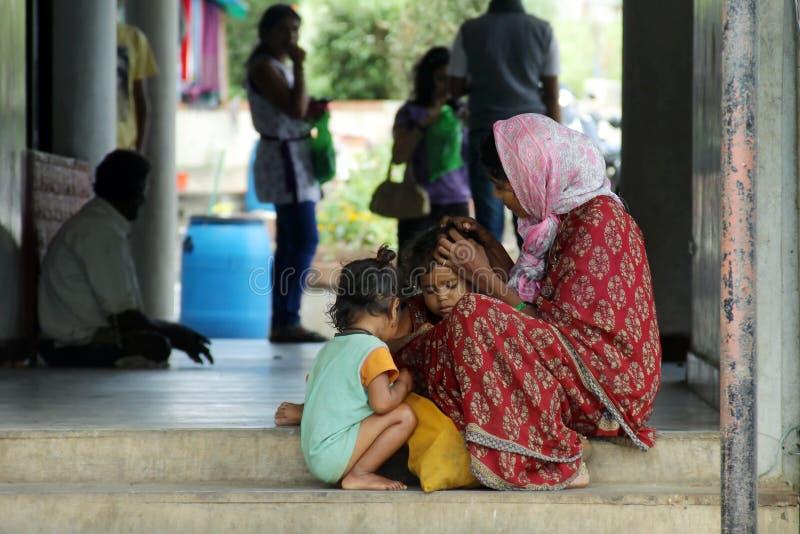 Moederschap - een slechte Indische moeder behandelt haar kinderen op straat royalty-vrije stock foto