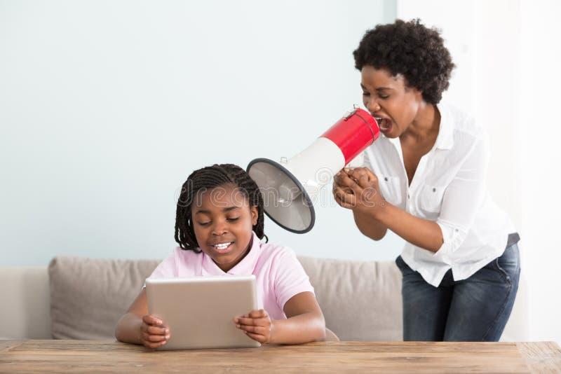 Moederschreeuwen bij Haar Dochter in een Megafoon stock afbeeldingen