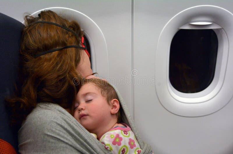 Moederslaap met haar baby tijdens vlucht stock afbeelding