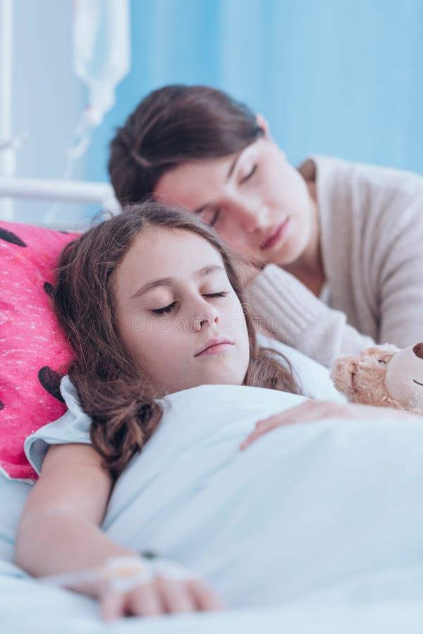 Moederslaap met zieke dochter royalty-vrije stock afbeeldingen