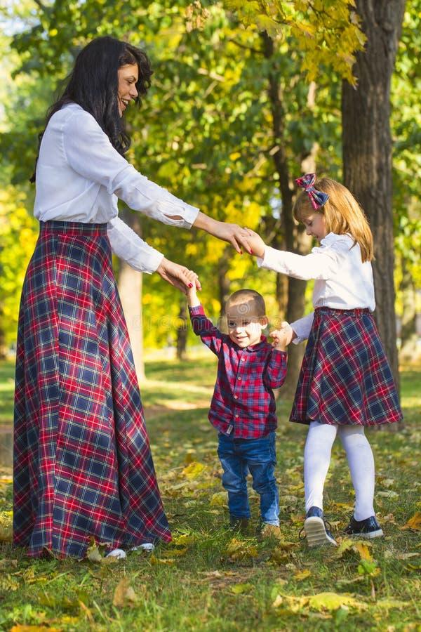 Moederspelen met haar kinderen in het park in de herfst stock afbeeldingen