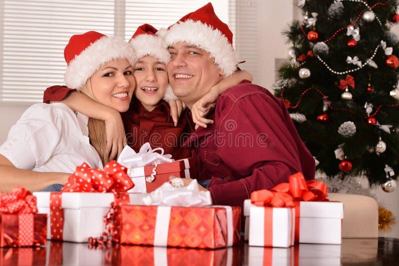 Moedervader en zoon dichtbij Kerstmisboom stock afbeelding