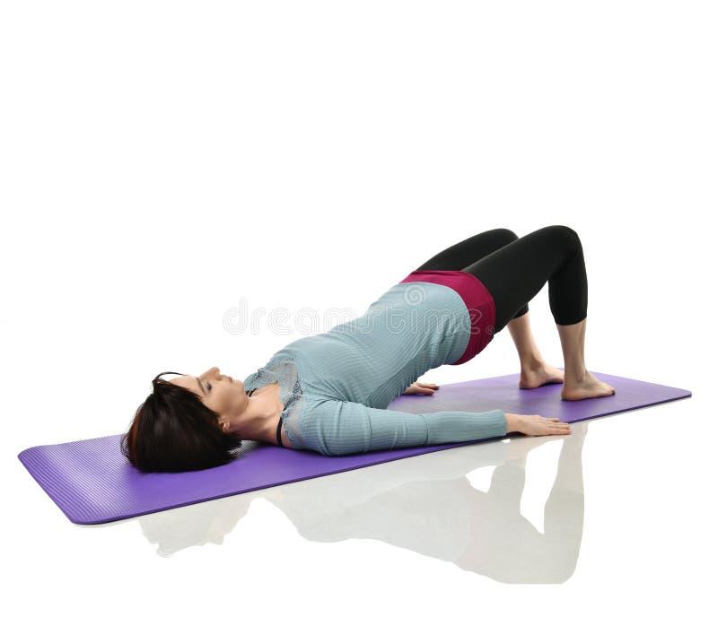 Moedervrouw die doend postnatale training uitoefenen De vrouwelijke geschiktheidsinstructeur houdt benen in gymnastiek en trainin stock afbeeldingen
