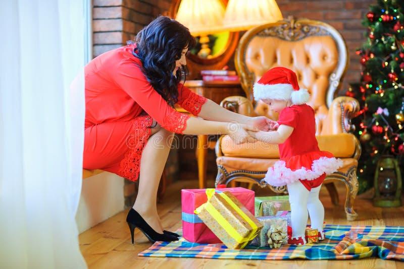 Moederzitting dichtbij venster het spelen met haar dochter die een Santa Clais-hoed dragen stock afbeeldingen