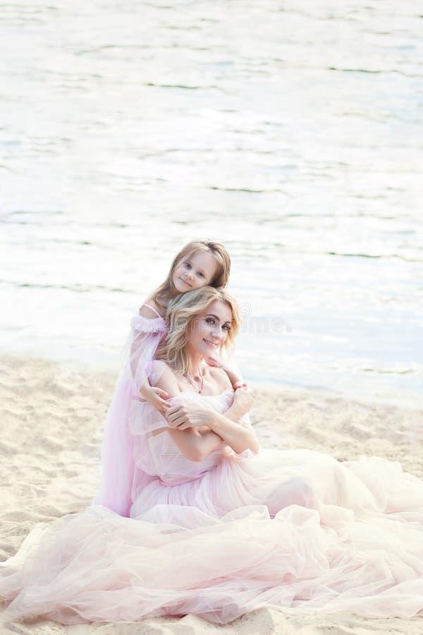 Moederzitting op het strand met een mooi meisje Kind die, het glimlachen, het lachen, de zomerdag koesteren Gelukkige kinderjaren stock afbeeldingen