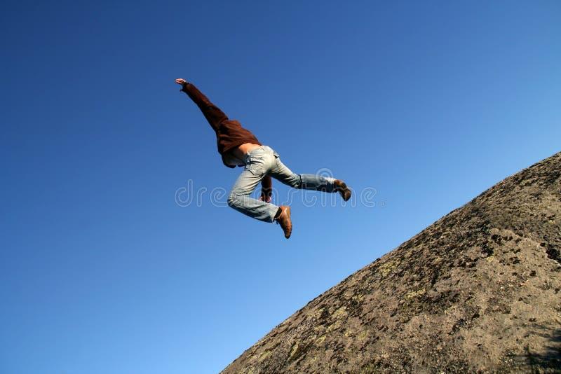 Moedige mens die van een klip springt royalty-vrije stock afbeelding