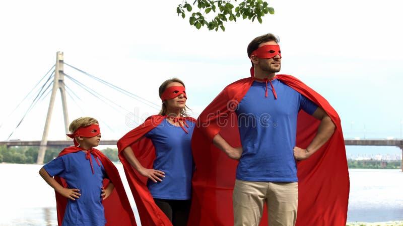 Moedige superherofamilie het letten op veiligheid van stad, krachtig team die naar overwinning gaan stock fotografie