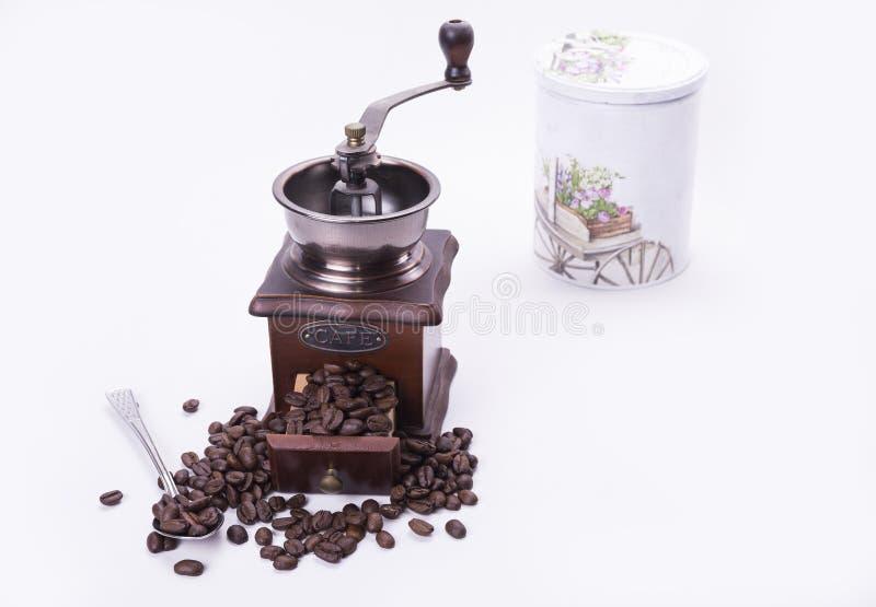 Moedor de café completamente de feijões roasted com a colher no backgro branco fotografia de stock