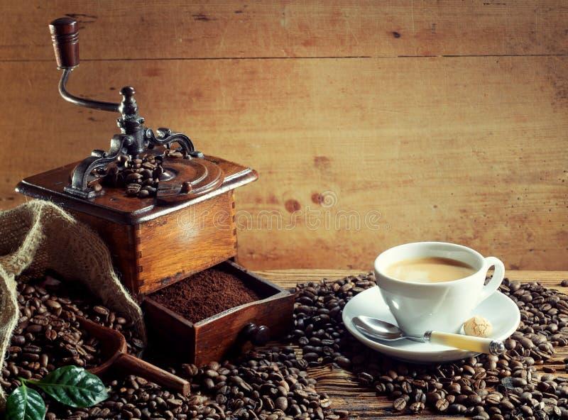 Moedor de café de madeira velho com xícara de café fotografia de stock