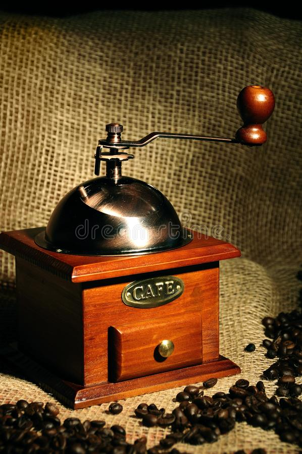 Moedor de café manual do vintage velho com feijões de café foto de stock