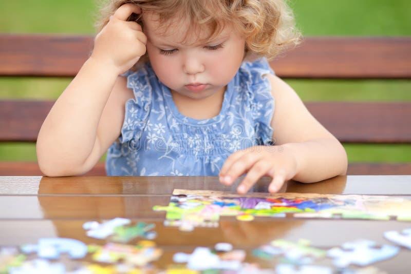 Moeilijke taak Vermoeide kind het spelen figuurzaag met ernstig gezicht stock foto's