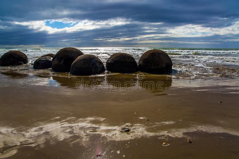 Moeraki's huge round boulders. The Pacific ocean tide begins. New Zealand. The sun's rays are reflected in the ocean water.  Moeraki's huge round boulders on a royalty free stock photography