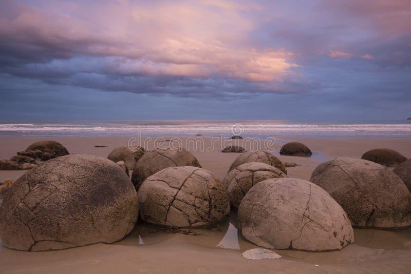 Moeraki stenblock på solnedgången, Nya Zeeland royaltyfri foto