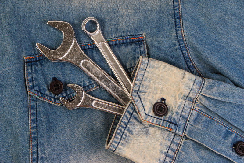 Moersleutelhulpmiddelen op een denimarbeiders, a-jeans met hulpmiddelen royalty-vrije stock foto