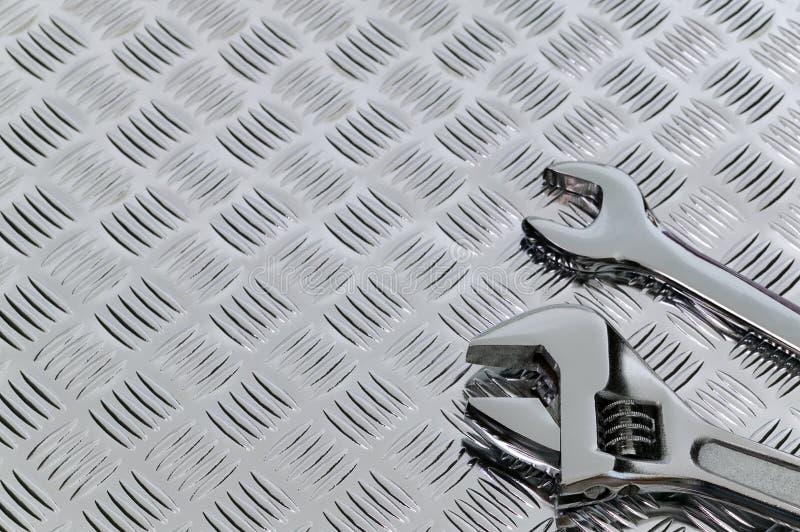 Moersleutels en checkerplate stock afbeelding