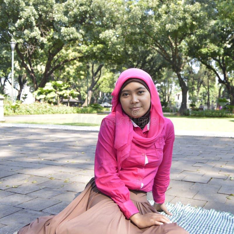 Moeslim-Mädchen, das am Park sitzt lizenzfreie stockfotos