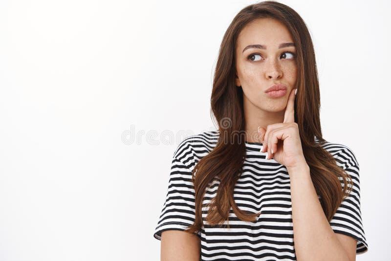 Moet je erover nadenken? Doordacht aantrekkelijke vrouwelijke vrouw met freckles in striped T-shirtplan, pouting royalty-vrije stock fotografie