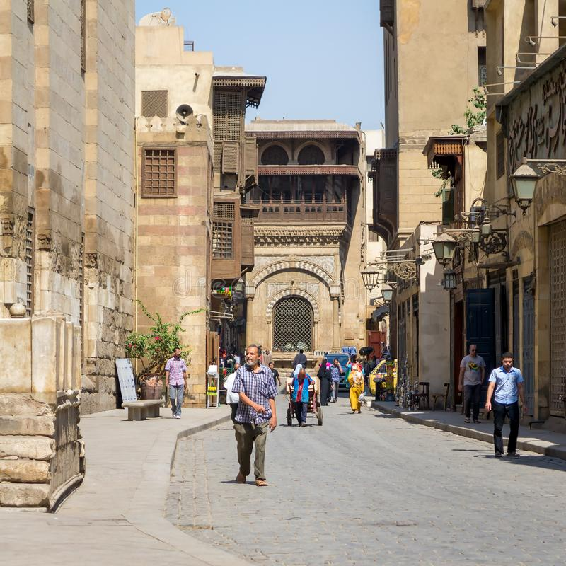 Moez Street with Sabil-Kuttab of Katkhuda historic building at the far end, Cairo, Egypt. Moez Street with local visitors and Sabil-Kuttab of Katkhuda historic stock photo