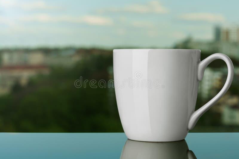 Mofa blanca en blanco de la taza para arriba en el alféizar al aire libre fotografía de archivo libre de regalías
