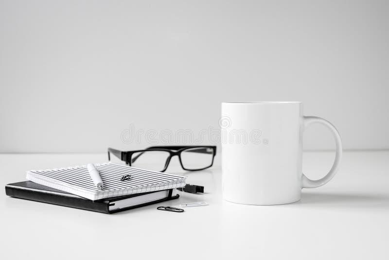 Mofa blanco y negro de la taza de café para arriba con los cuadernos, la pluma y las lentes imágenes de archivo libres de regalías
