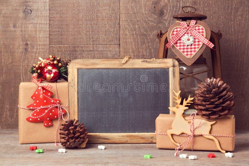 Mofa de la pizarra para arriba con los regalos de la Navidad y las decoraciones rústicas imagen de archivo