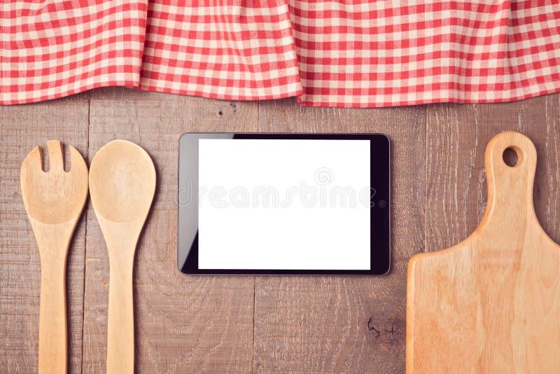Mofa de la tableta de Digitaces encima de la plantilla con los utensilios y el mantel de la cocina Visión desde arriba fotos de archivo libres de regalías