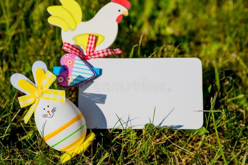 Mofa de la tarjeta de felicitación de Pascua para arriba con los huevos del conejito en fondo de la hierba verde Concepto creativ imagen de archivo