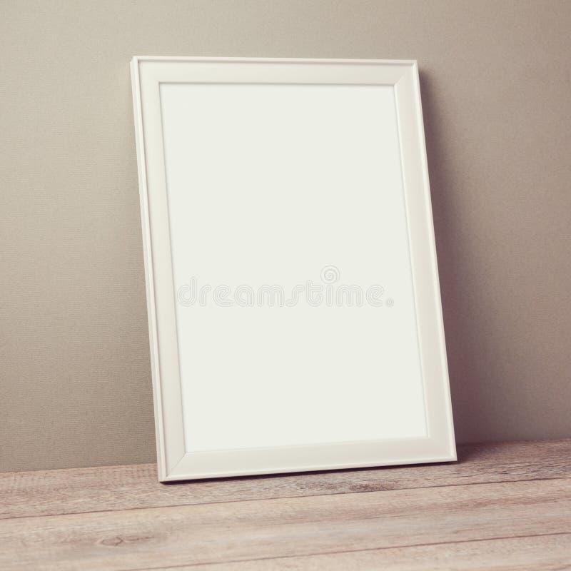 Mofa del marco del cartel encima de la plantilla en piso de madera foto de archivo libre de regalías